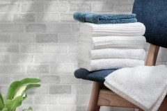 Clean terry towels on wooden chair with brick wall background, copy space.